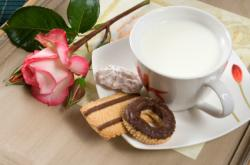 Milk cup with rose flower and chocolate biscuits